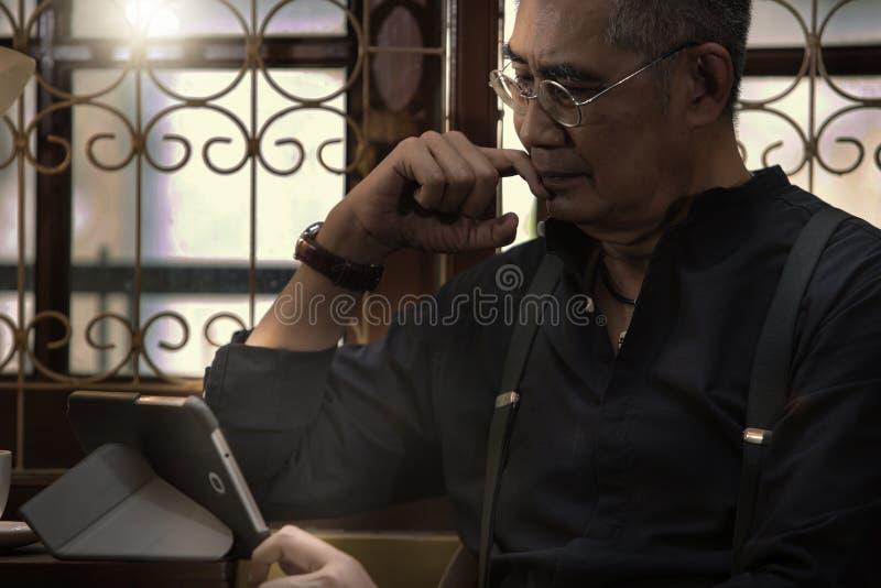 Leitura do homem de negócios em um PC da tabuleta imagens de stock royalty free