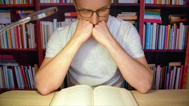 Leitura do homem na mesa com lâmpada imagens de stock royalty free
