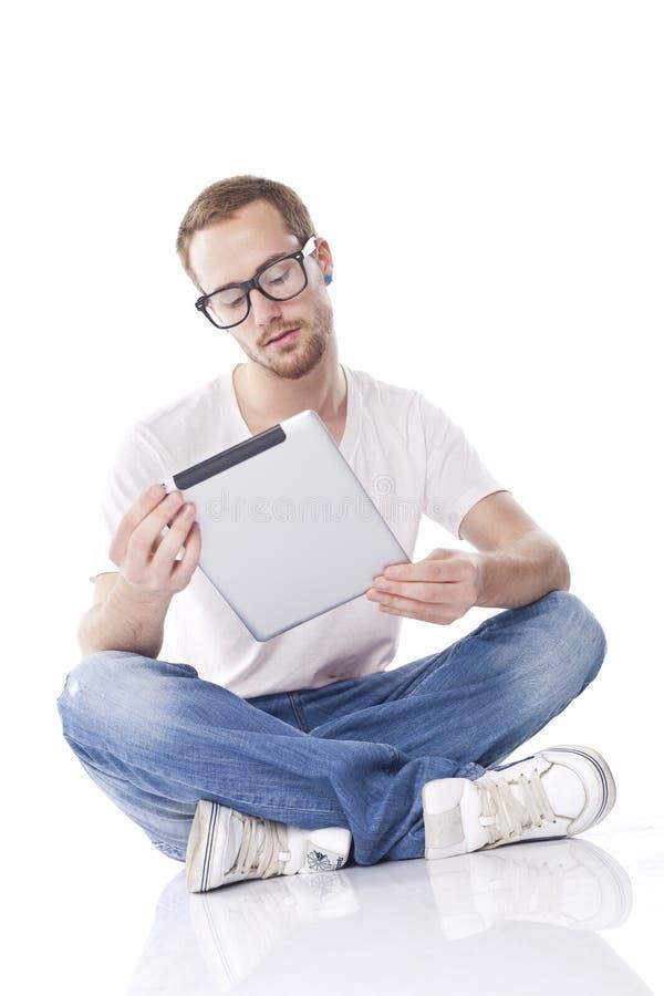 Leitura do homem no computador da tabuleta fotografia de stock royalty free