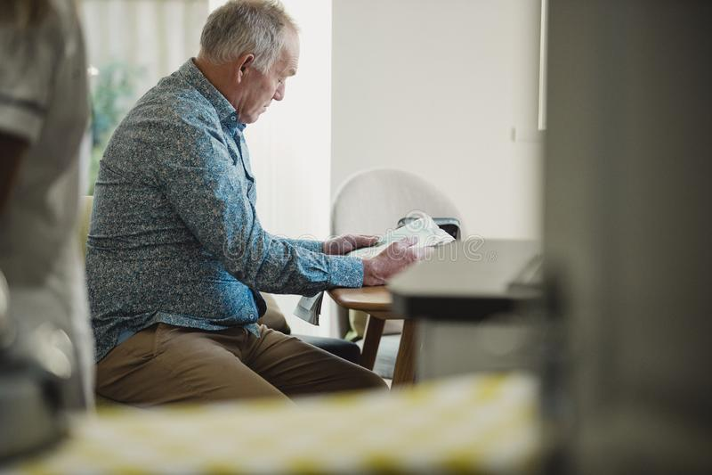 Leitura do homem superior na casa do cuidado imagens de stock royalty free