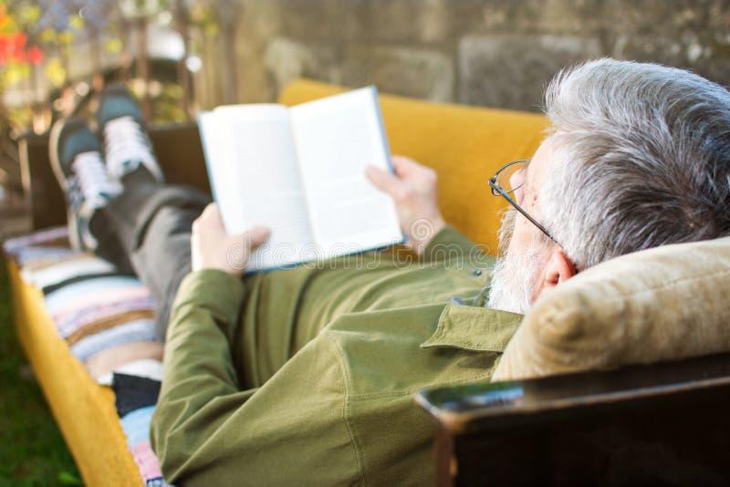 Leitura do homem superior que encontra-se na cama na jarda fotografia de stock