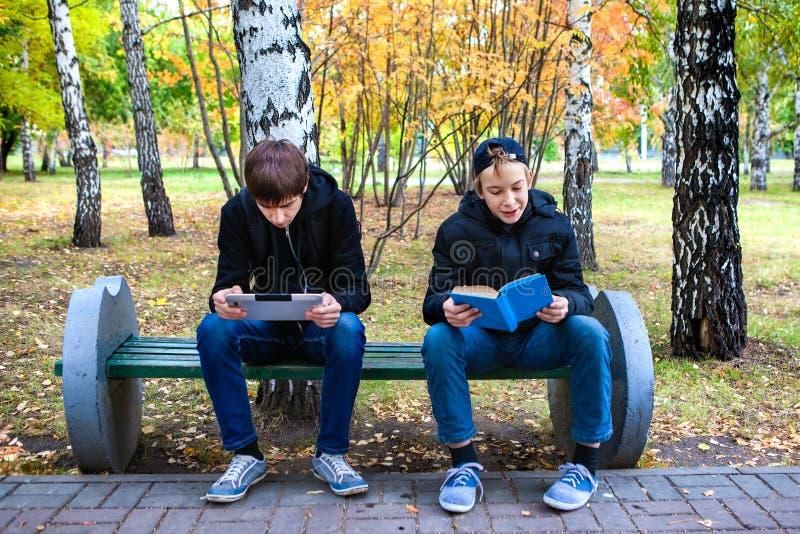 Leitura dos meninos exterior imagens de stock