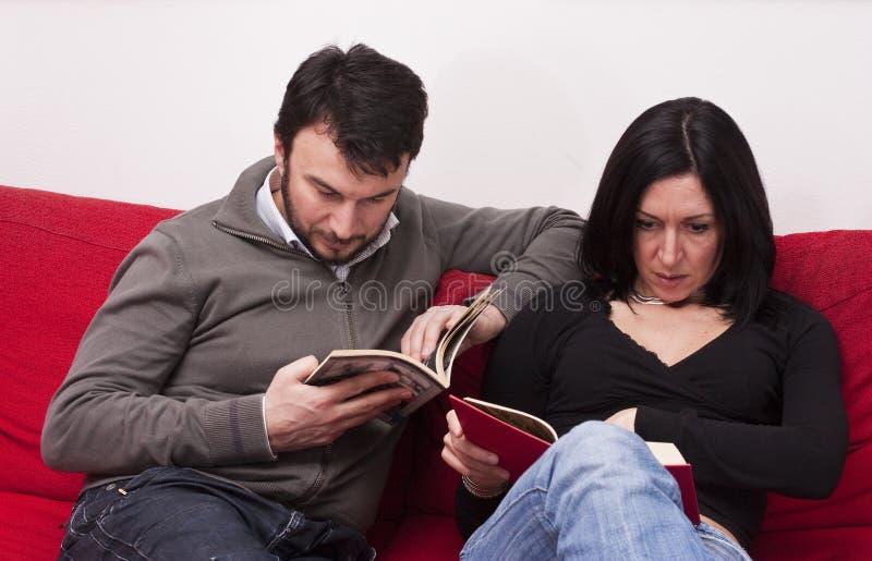Leitura dos pares em casa imagens de stock royalty free