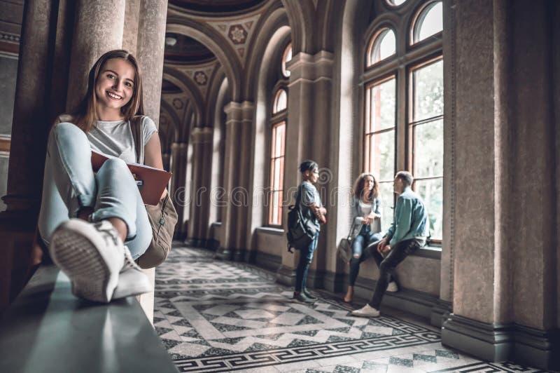 Leitura durante uma ruptura Estudante bonito que prepara-se à lição ao sentar-se nos trilhos imagens de stock royalty free