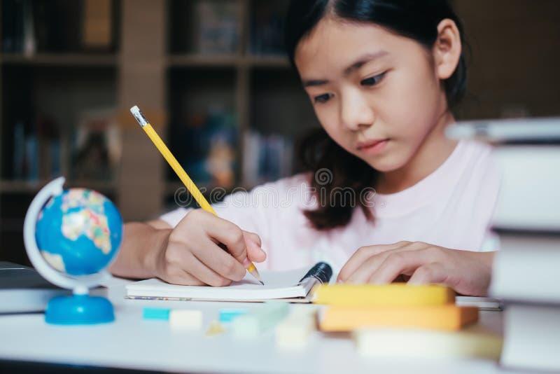 A leitura e a escrita da menina e fazem trabalhos de casa na biblioteca foto de stock