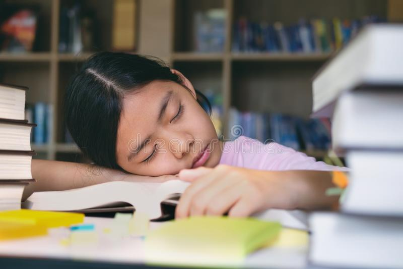 A leitura e a escrita da menina e fazem trabalhos de casa na biblioteca imagem de stock