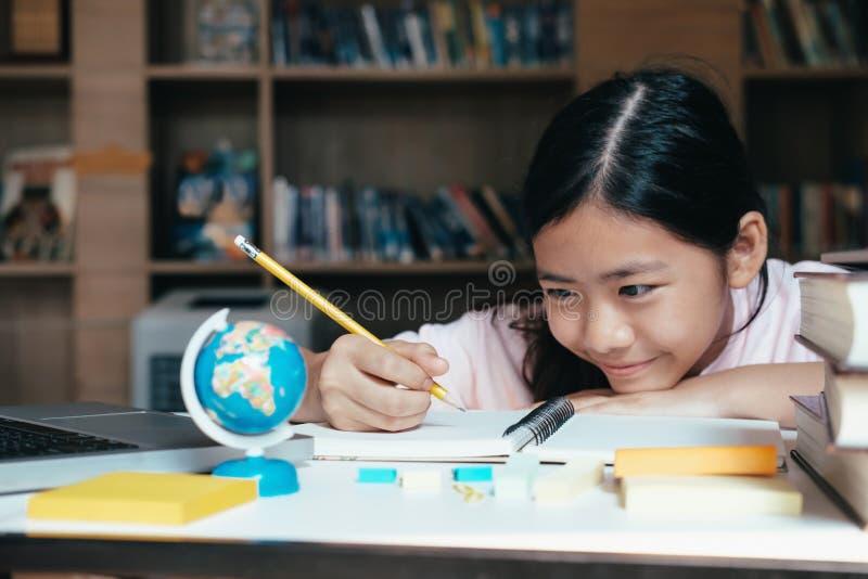 A leitura e a escrita da menina e fazem trabalhos de casa na biblioteca fotos de stock
