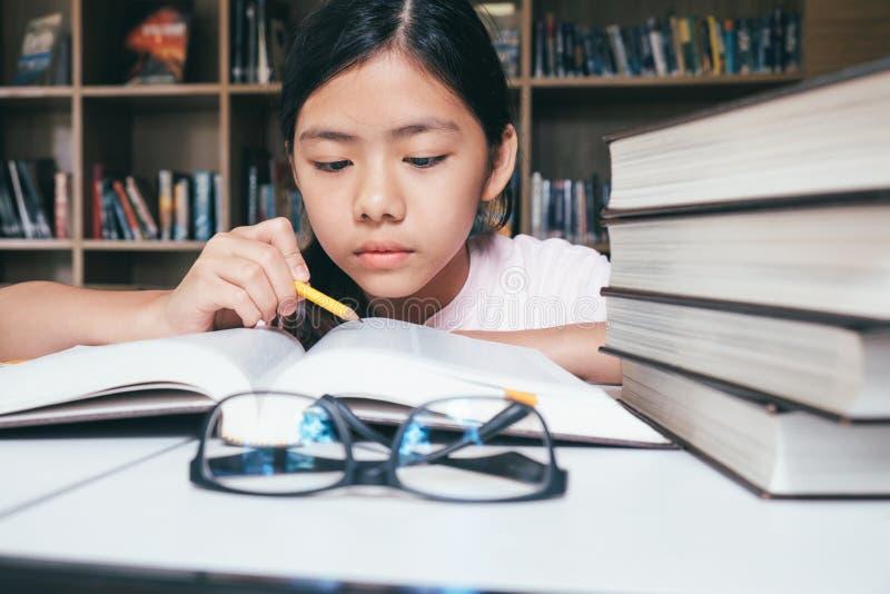 A leitura e a escrita da menina e fazem trabalhos de casa na biblioteca fotografia de stock