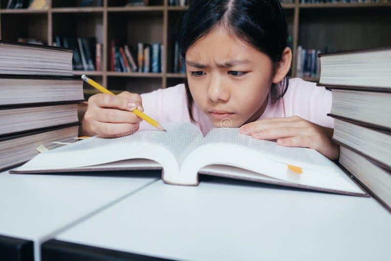 A leitura e a escrita da menina e fazem trabalhos de casa na biblioteca fotos de stock royalty free