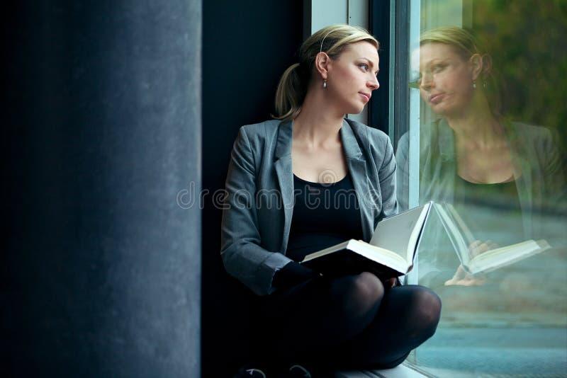 Leitura e sonho sós da mulher foto de stock royalty free