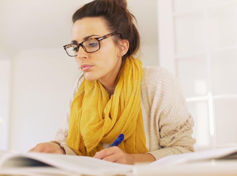 Leitura esperta da mulher ao tomar notas fotografia de stock royalty free