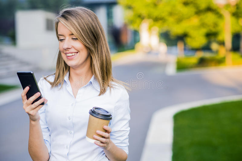 Leitura esperta nova da mulher profissional usando o telefone Notícia fêmea da leitura da mulher de negócios ou sms texting no sm fotos de stock royalty free