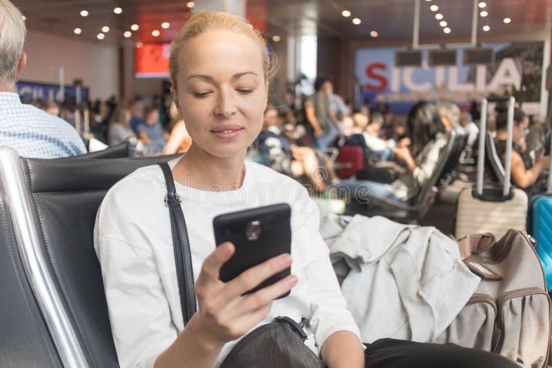 Leitura f?mea do viajante em seu telefone celular ao esperar para embarcar um plano em portas de partida no terminal de aeroporto fotografia de stock royalty free