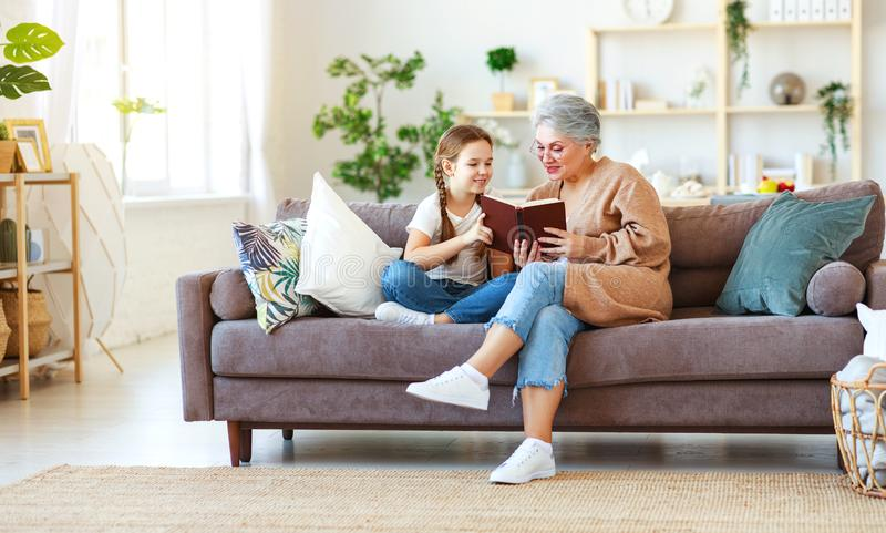 Leitura feliz da avó da família ao livro da neta em casa imagens de stock