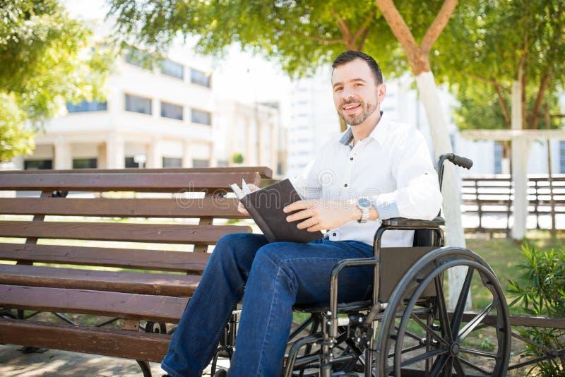 Leitura feliz do homem em um parque imagens de stock royalty free