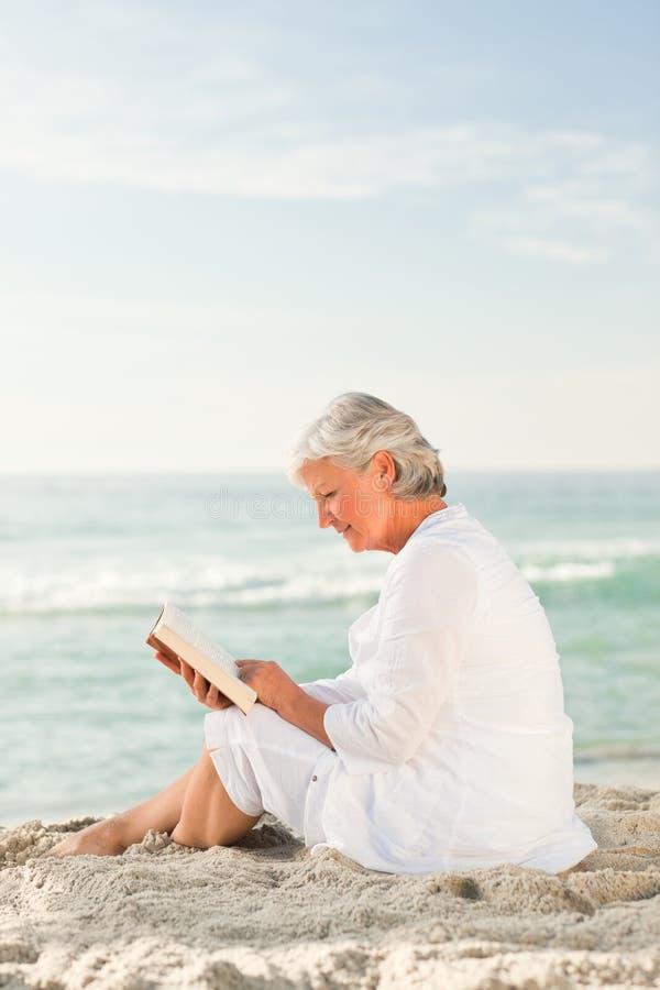 Leitura idosa da mulher seu livro imagens de stock royalty free