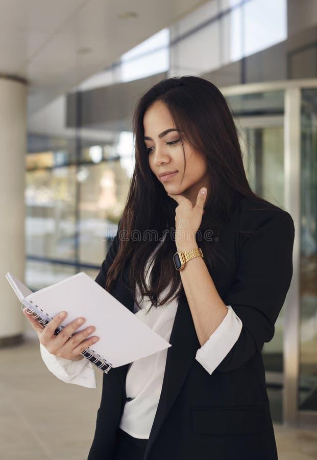 Leitura latino-americano da mulher de negócio algo em um livro da cópia fotografia de stock royalty free