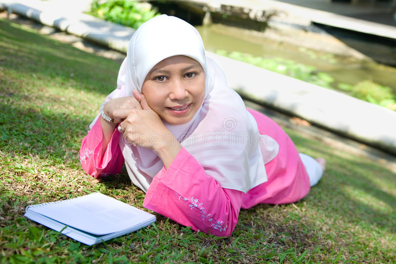 Leitura muçulmana da mulher do Malay asiático foto de stock