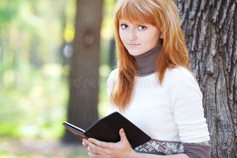 Leitura nova bonita da mulher do adolescente do redhead imagens de stock