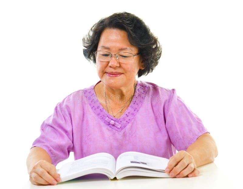 Leitura séria da mulher sênior asiática foto de stock royalty free