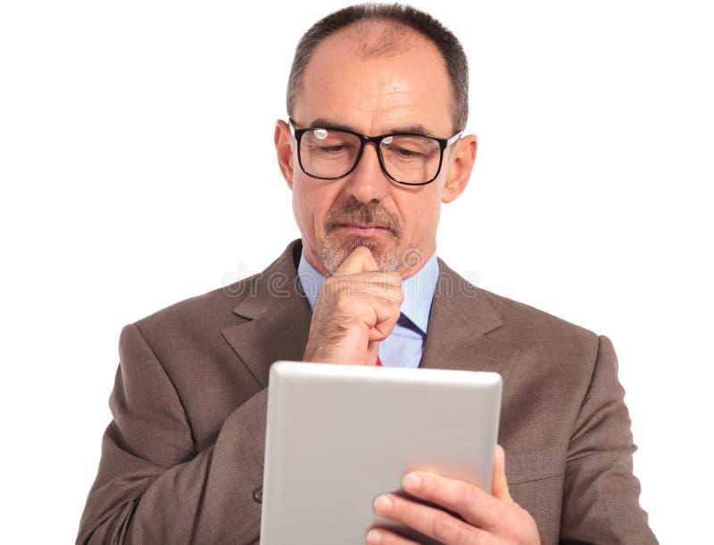 Leitura superior pensativa do homem de negócios em sua tabuleta fotografia de stock royalty free
