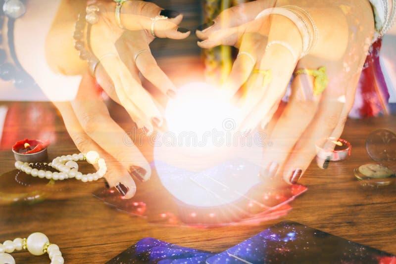 Leituras psíquicos e conceito da clarividência - mãos do caixa de fortuna da bola de cristal e cartões de tarô que leem a adivinh imagens de stock