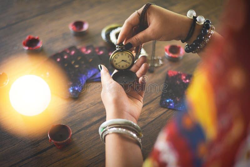 Leituras psíquicos e conceito da clarividência - o caixa de fortuna da bola de cristal com mãos guarda a leitura retro do relógio imagem de stock royalty free