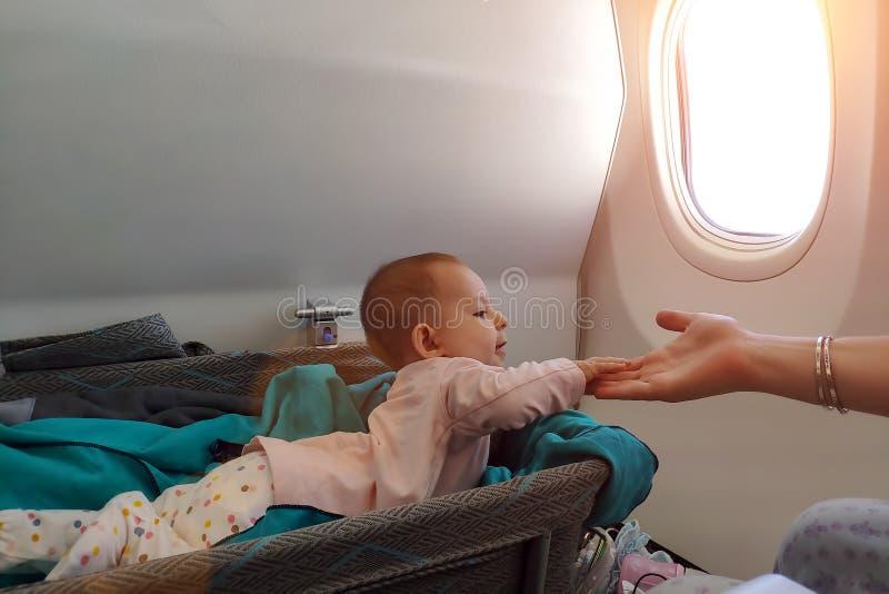 Lejías infantiles felices del bebé en cuna especial en aeroplano en su estómago Primer vuelo del bebé, la impresionan y el sosten foto de archivo
