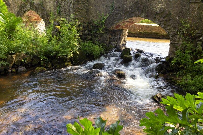 Leje się spływanie pod mostem na słonecznym dniu fotografia stock