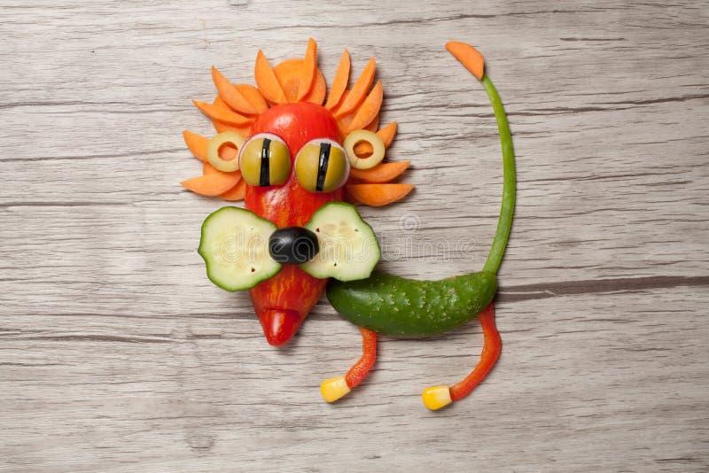 Lejon som göras av grönsaker på träbakgrund arkivfoton