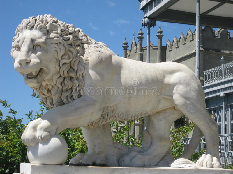 Lejonskulptur som göras av vit marmor mot bakgrunden av den gamla slotten royaltyfria bilder