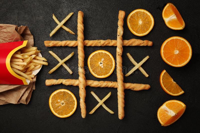 Lek av muskelryckningtac-tån av franska småfiskar och apelsinen Välja som är sunt vs sjukliga foods Färdigt eller fett begrepp royaltyfri fotografi