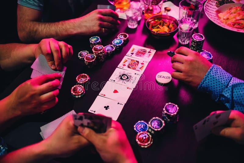 Lek av pokerkort och chiper på tabellen med händerna av spelarna royaltyfri bild