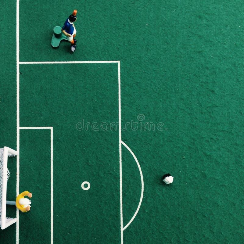 Lek för mottagningsrum för Tipp sparkfotboll med grön bakgrund en målvakt i ett mål och en fotbollsspelare fotografering för bildbyråer
