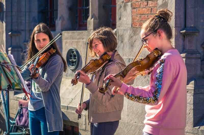 Lek för tre lycklig kvinnlig tonårig violinister för donation royaltyfri foto