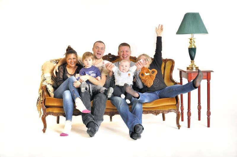 Lek för två ung familjer som dumbommen med ett barn sitter på en soffa arkivbilder