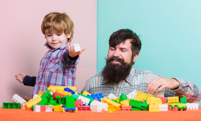 Lek f?r fadersonlek Fadern och sonen skapar f?rgrika konstruktioner med tegelstenar Barnav?rdutveckling och uppfostran royaltyfri bild