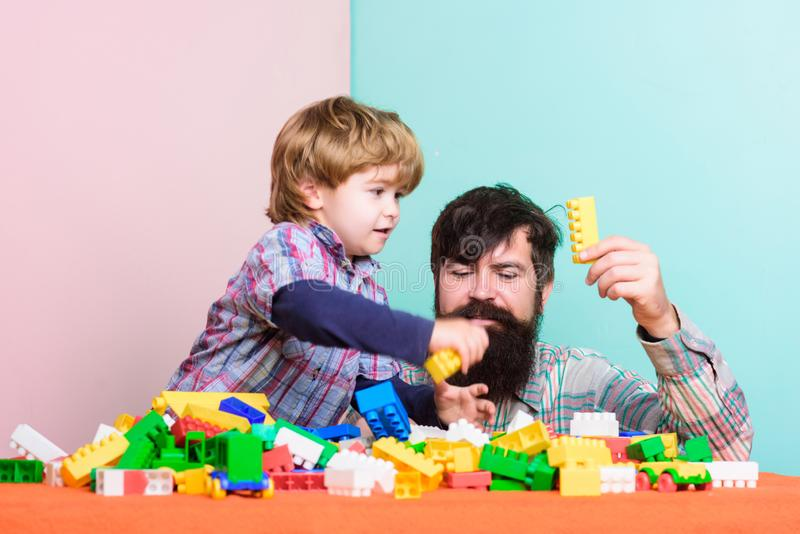 Lek f?r fadersonlek Farsa- och ungebyggande av plast- kvarter Fadern och sonen skapar f?rgrika konstruktioner med tegelstenar arkivbilder