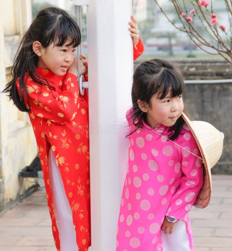 Lek och skratt för två liten vietnamesisk flickor i nationella dräkter fotografering för bildbyråer