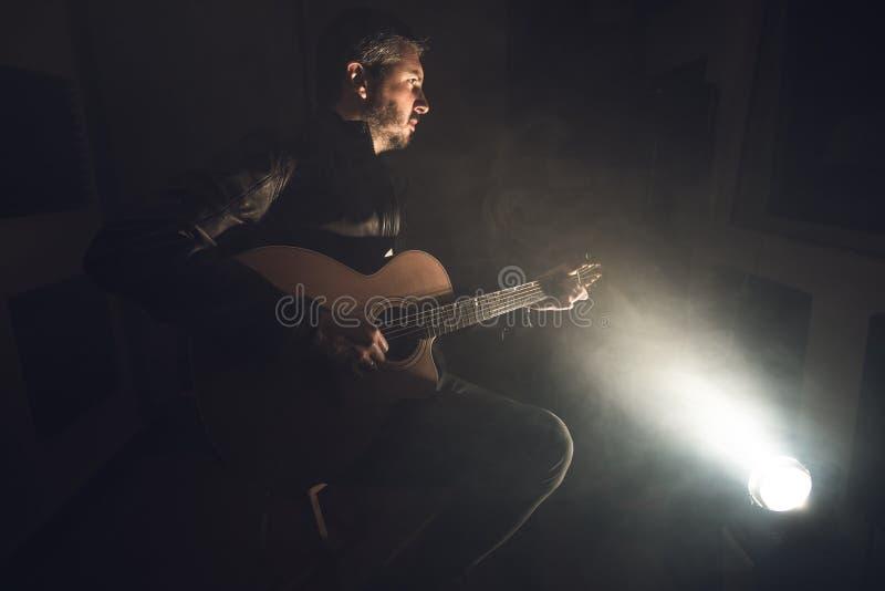 leka för gitarrman Gitarristen arrangerar på arkivfoto