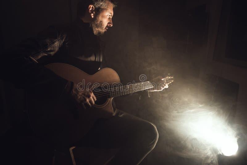leka för gitarrman Gitarristen arrangerar på royaltyfri fotografi