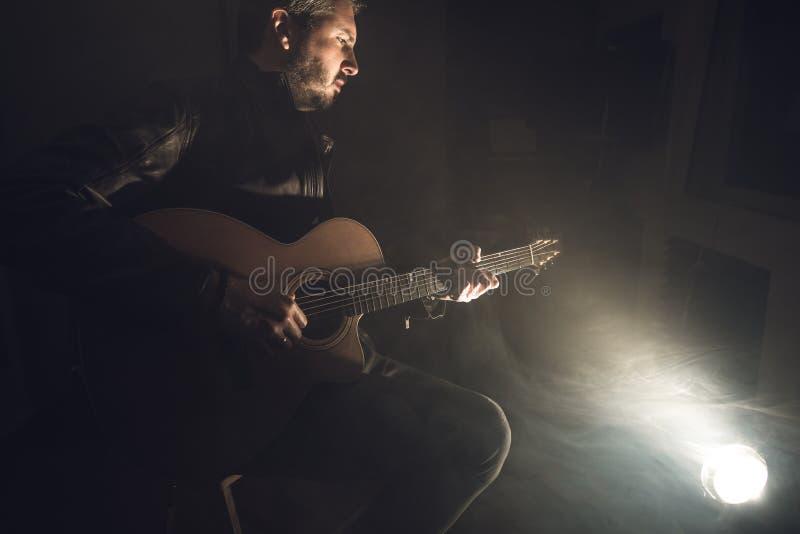 leka för gitarrman Gitarristen arrangerar på royaltyfria foton