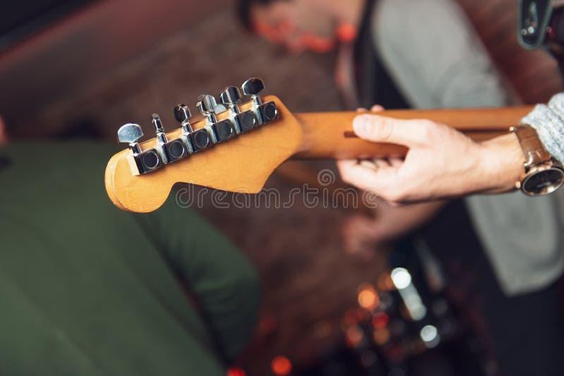 leka för gitarrman Hals- och handcloseup royaltyfri foto