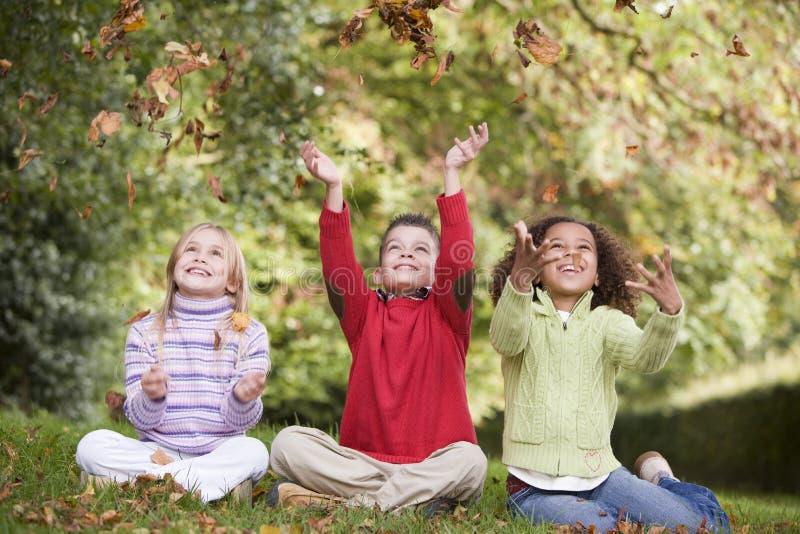 leka för leaves för höstbarngrupp fotografering för bildbyråer