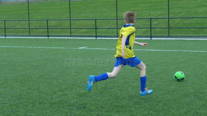 leka fotboll för pojke royaltyfria bilder
