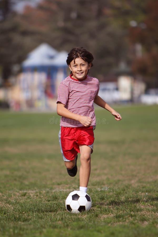 Leka fotboll för pojke i parkera arkivfoton