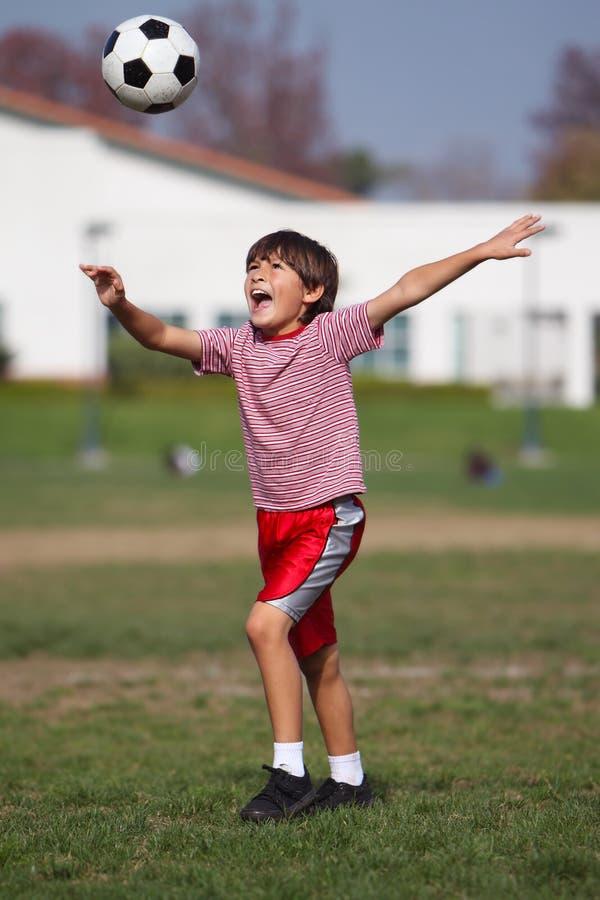 Leka fotboll för pojke i parkera arkivbild