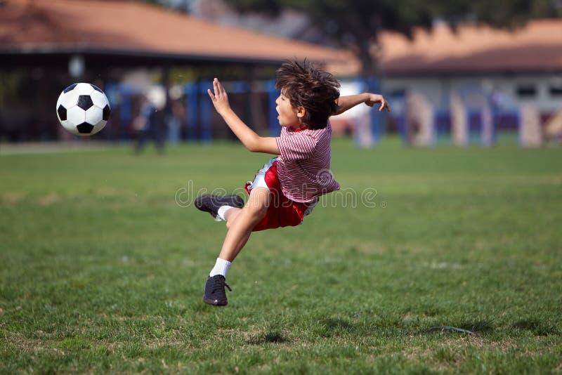 Leka fotboll för pojke i parkera royaltyfri fotografi