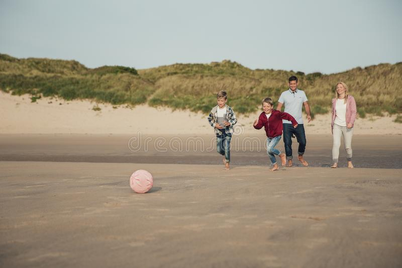 Leka fotboll på stranden royaltyfria bilder