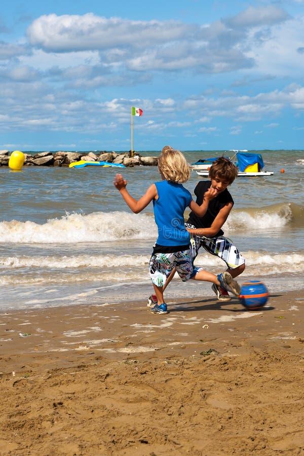 Leka fotboll på stranden arkivbilder